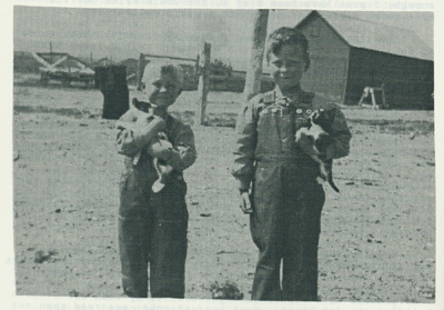 Lawrence and Jim Metzger on farm at an early age, wearing red shirts.