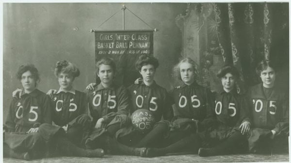 black and white photograph taken in 1901 or 1902; seven women in dark uniforms, basketball in lap