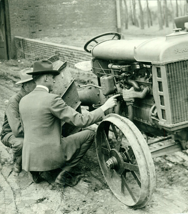 A photograph of two men crouching next to a Ford tractor