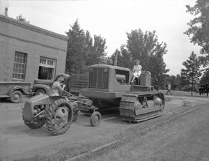 A photograph of two women riding tractors and facing each other